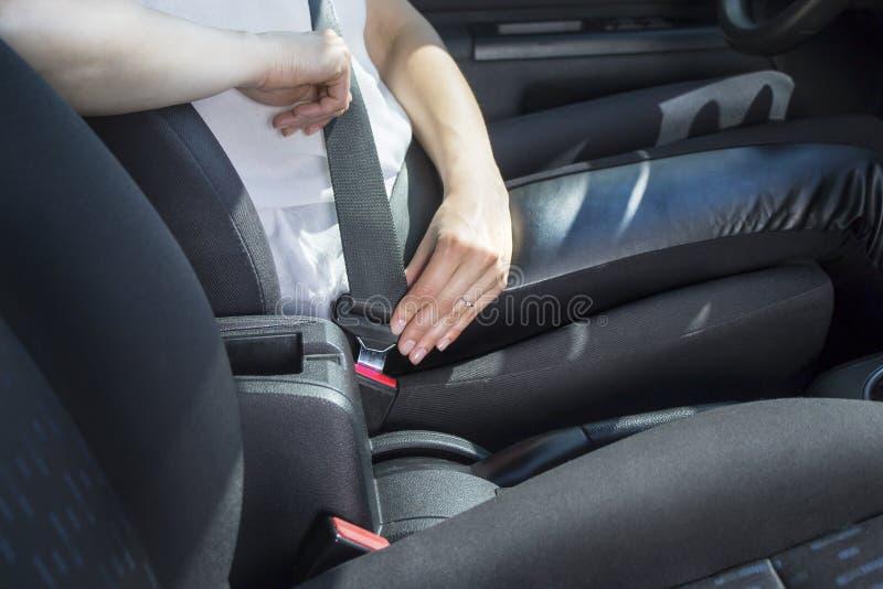妇女在客车的轮子后坐并且紧固安全带 免版税库存图片