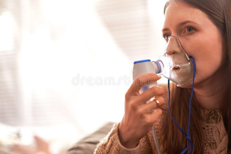 妇女在家做吸入雾化器 拿着吸入发烟的面具雾化器喷洒疗程入病您的肺 库存照片