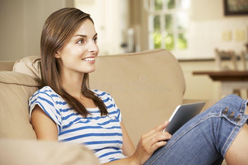 妇女在家坐沙发使用片剂计算机,看电视 库存图片