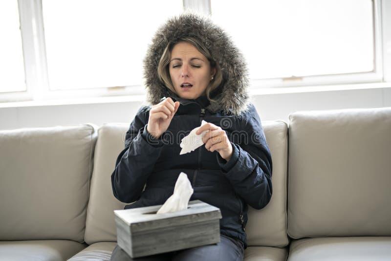 妇女在家有在沙发的流感有冬天外套的 图库摄影