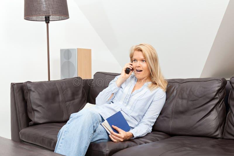 妇女在家谈话在电话 免版税库存图片