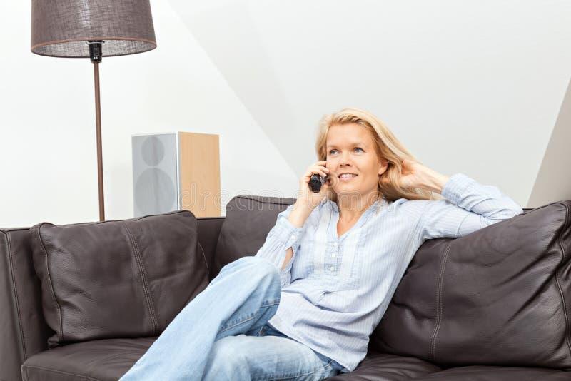 妇女在家谈话在电话 免版税图库摄影