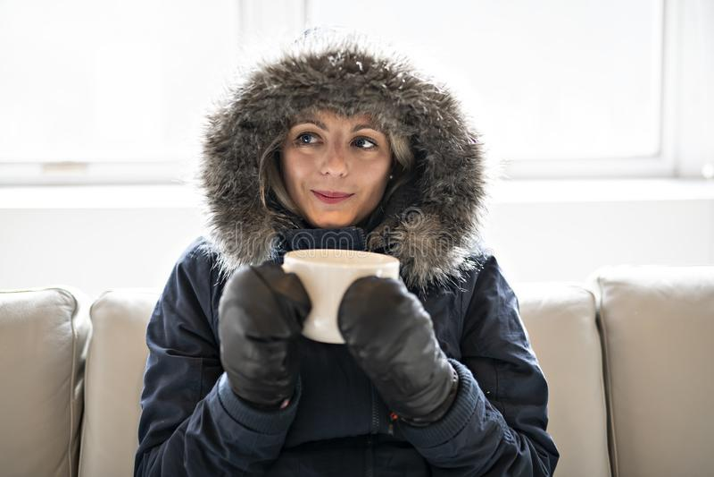 妇女在家食用在沙发的冷的饮料咖啡有冬天外套的 免版税库存图片