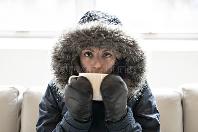 妇女在家食用在沙发的冷的饮料咖啡有冬天外套的 库存照片
