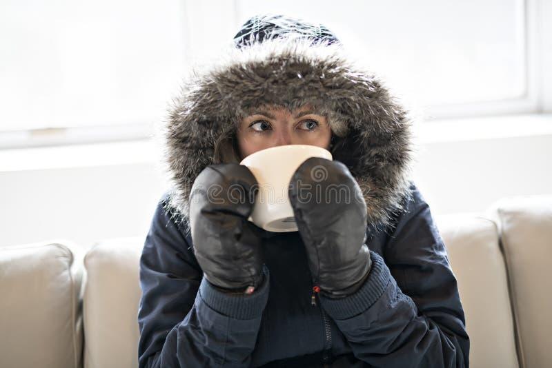 妇女在家食用在沙发的冷的饮料咖啡有冬天外套的 免版税库存照片