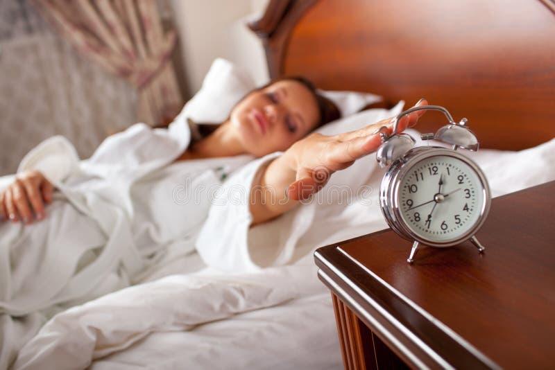 妇女在对闹钟的床延伸的手上 库存图片