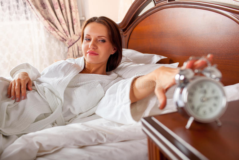 妇女在对闹钟的床延伸的手上 图库摄影