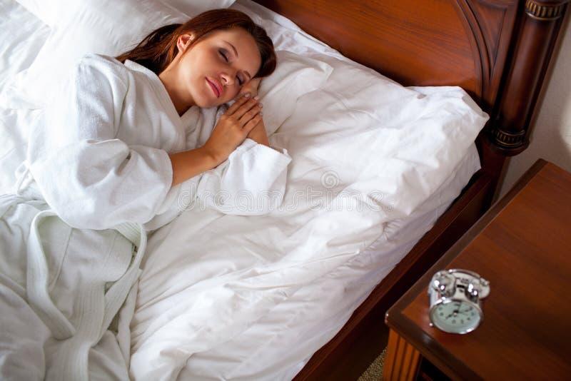 妇女在对闹钟的床延伸的手上 库存照片