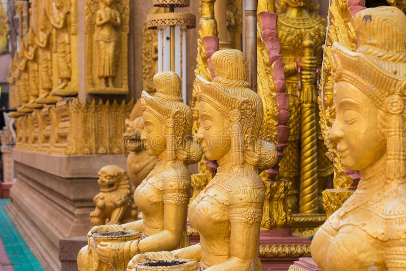 妇女在寺庙的金雕象 Ubonratchathani泰国 免版税库存照片