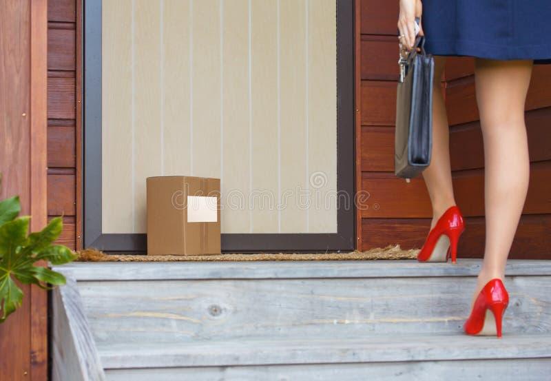 妇女在工作以后到家对与标签的交付小包门 免版税库存图片