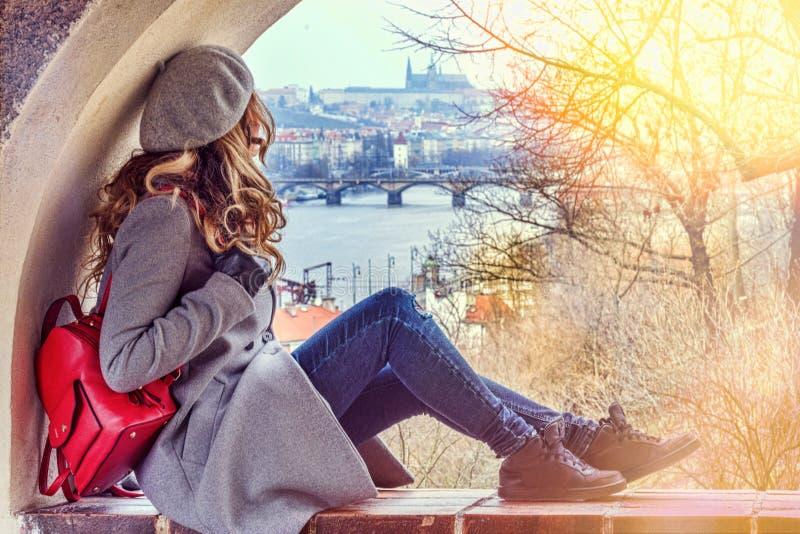 妇女在布拉格, Czeh共和国 在灰色打扮的美丽的金发碧眼的女人 城堡背景视图 免版税库存图片