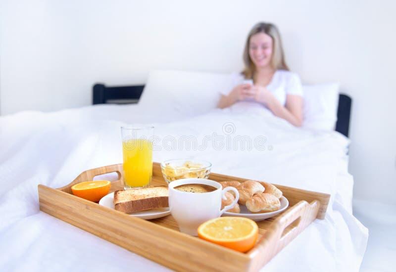 妇女在床上的吃早餐 库存照片