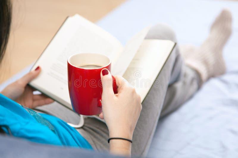 妇女在床上的读一本书 库存照片