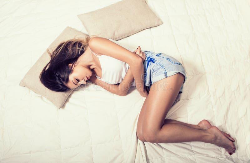 妇女在床顶视图的胃痛 图库摄影
