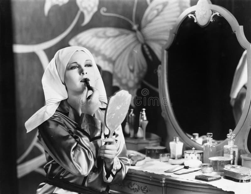 妇女在应用化妆用品的梳妆台上 免版税库存图片