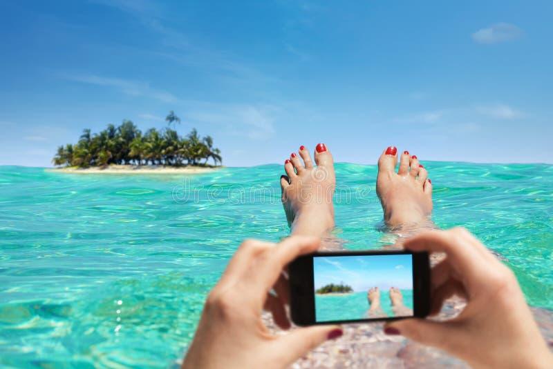 妇女在度假与智能手机的拍一张照片 免版税库存图片