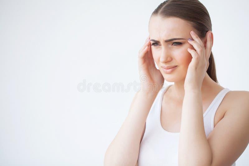 妇女在感到的痛苦中坏和恶心,有头疼和热病,握在前额的手 美丽的不快乐的疲乏的女孩 库存照片