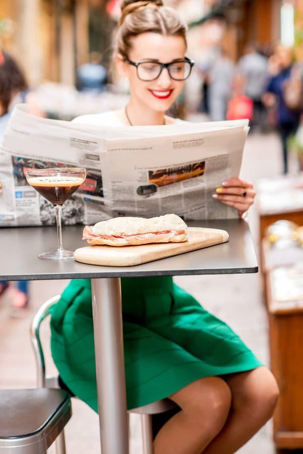 妇女在户外咖啡馆的读书报纸 图库摄影