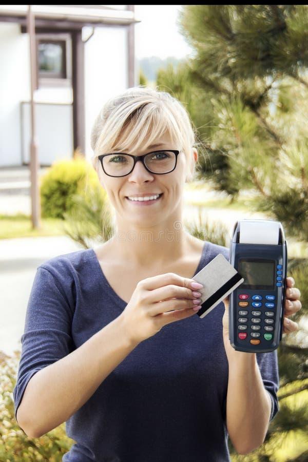 妇女在房子的手上拿着付款终端 买家和不动产的概念 库存照片
