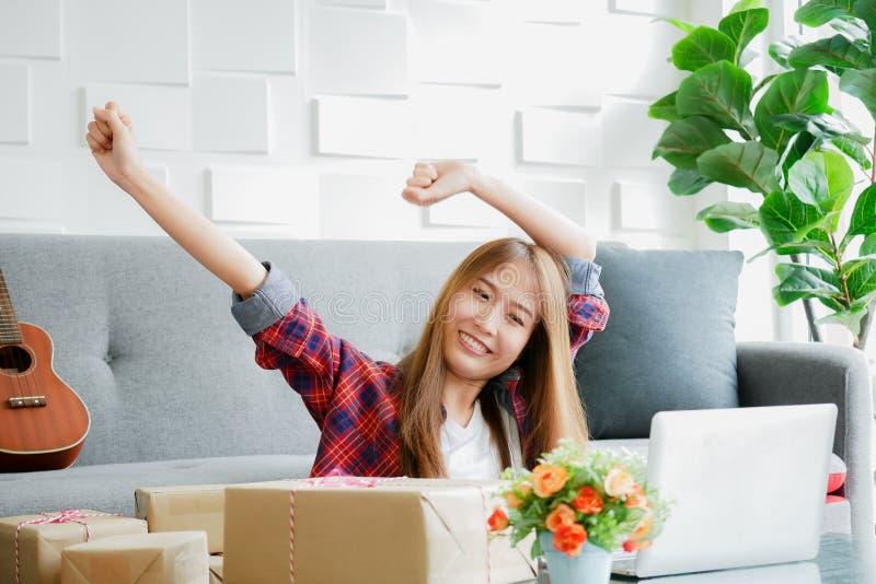 妇女在房子里微笑与胳膊的面孔举与包含她的产品的箱子将被交付到在书桌上的顾客 库存图片