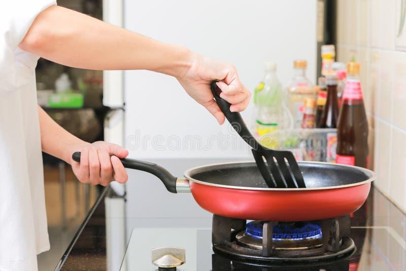 妇女在手上的拿着一个平底锅烹调煎蛋卷在厨房里 库存图片