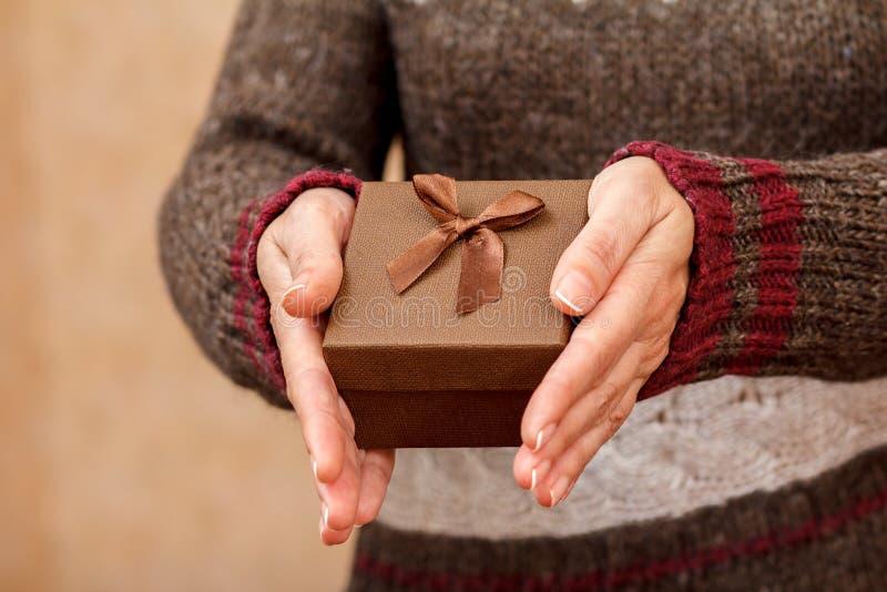 妇女在手上的拿着一个棕色礼物盒 免版税库存照片