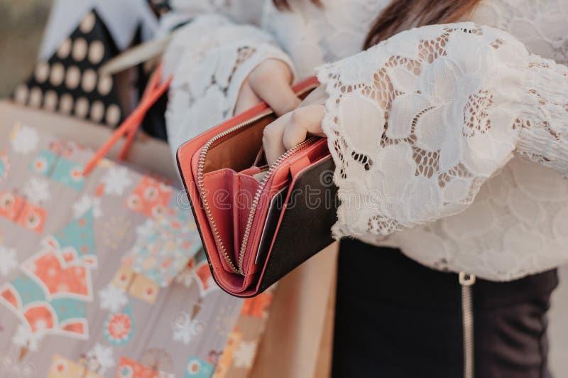 妇女在手上的拿着一个黑钱包 免版税库存照片