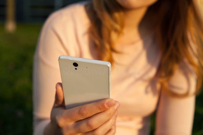 妇女在手上的拿着智能手机 免版税库存图片