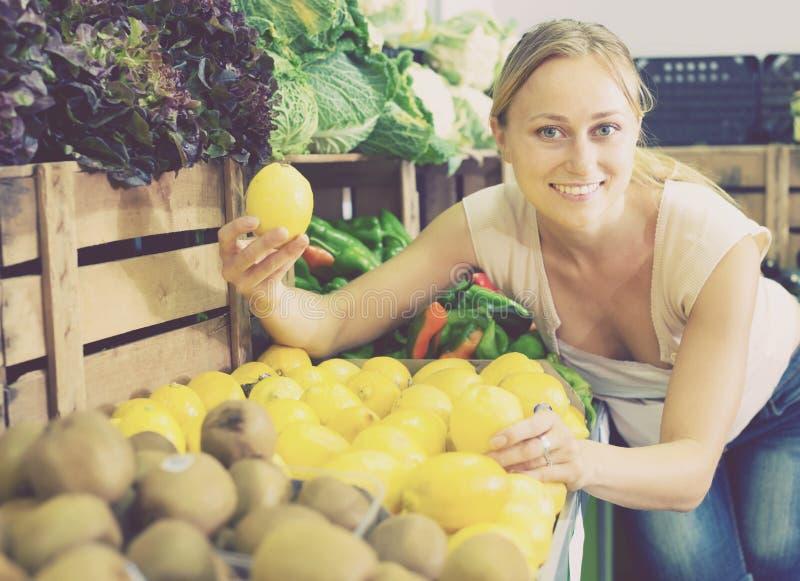妇女在手上的拿着柠檬在果子商店 库存图片