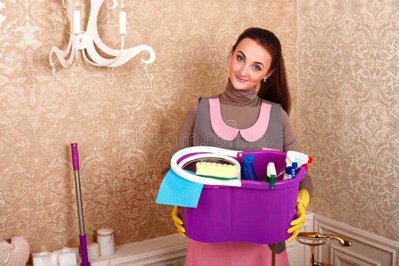 妇女在手上的拿着清洁物品 库存图片