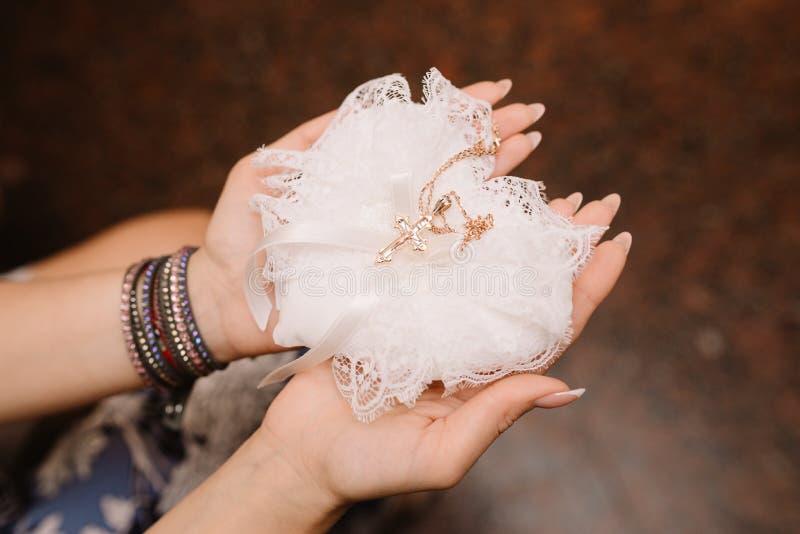 妇女在手中拿着与链子的一个金十字架 洗礼仪式 免版税图库摄影