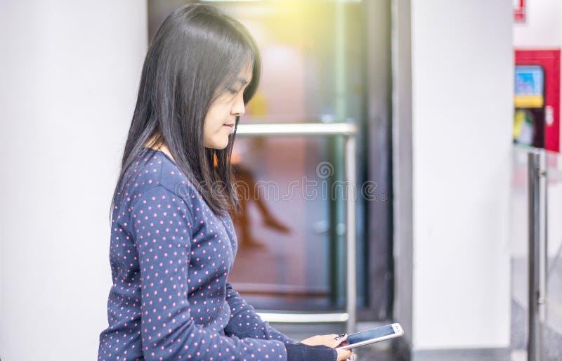 妇女在手机的检验飞行数字在机场 库存图片