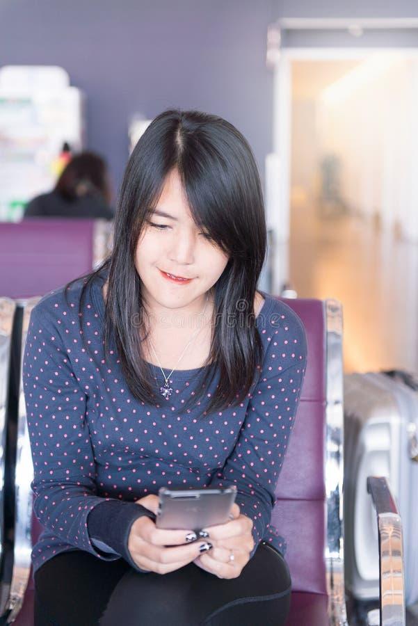 妇女在手机的检验飞行数字在机场 免版税库存图片
