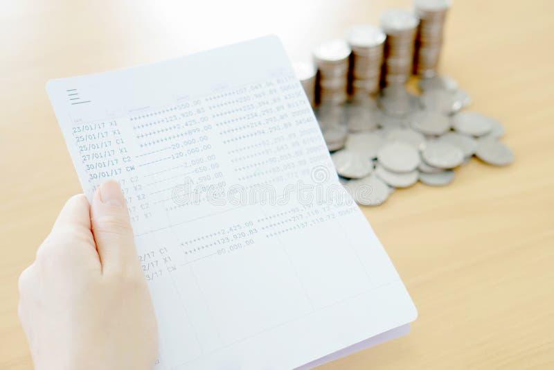 妇女在手边举行存款簿,硬币 库存照片