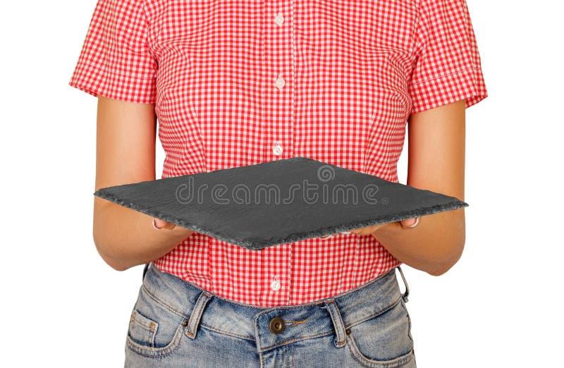 妇女在拿着一个方形的板岩盛肉盘或一个委员会在她前面的衬衣穿戴了 您的设计的透视图模板 isola 免版税库存照片