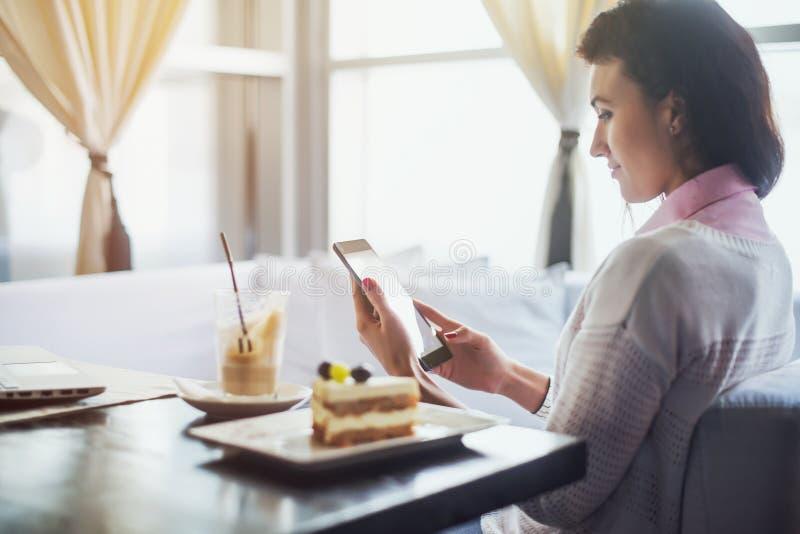妇女在拿着数字式片剂,浏览互联网的餐馆或连接到无线侧视图 图库摄影