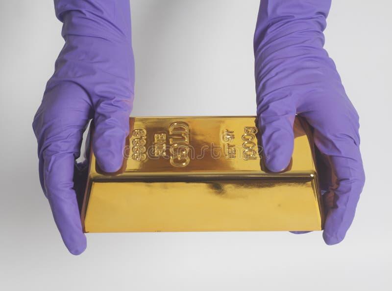 妇女在拿着金锭的紫色手套的` s手 免版税图库摄影
