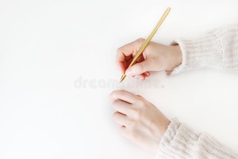 妇女在拿着金黄balpoint的毛线衣的` s手写作准备好文字,在白色背景隔绝的图画 教育 库存照片