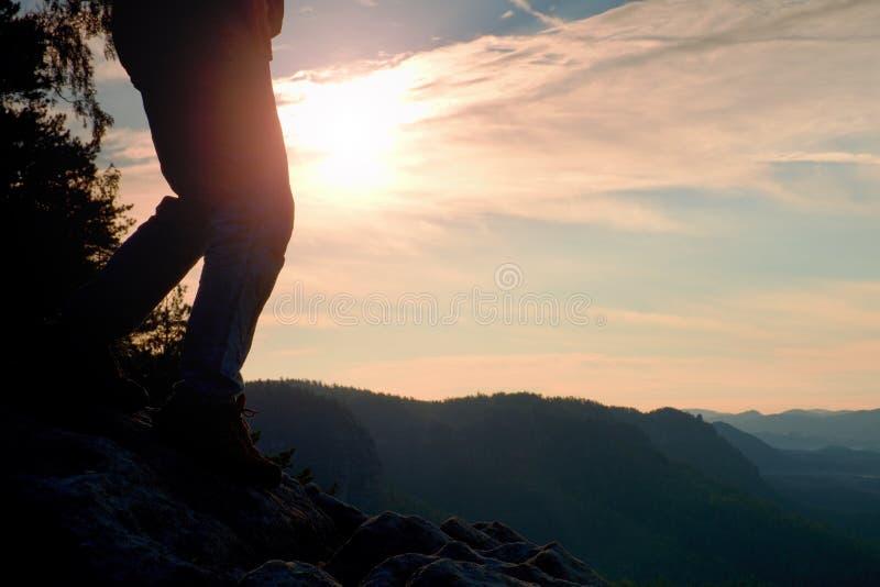 妇女在旅游起动的远足者腿在山岩石峰顶站立 太阳n背景 库存照片