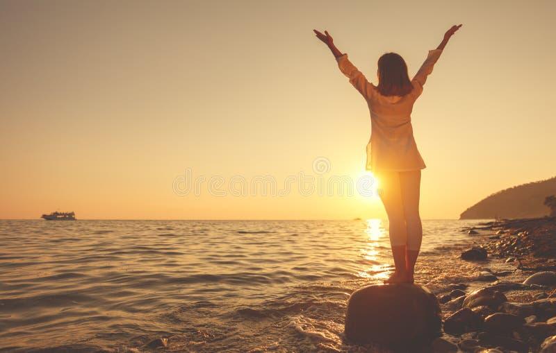 妇女在日落海滩实践瑜伽并且思考 免版税库存图片