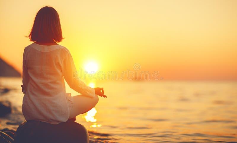 妇女在日落b的莲花坐实践瑜伽并且思考 免版税库存照片
