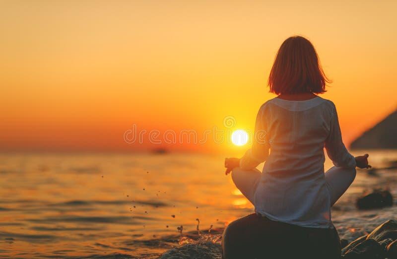 妇女在日落b的莲花坐实践瑜伽并且思考 免版税库存图片
