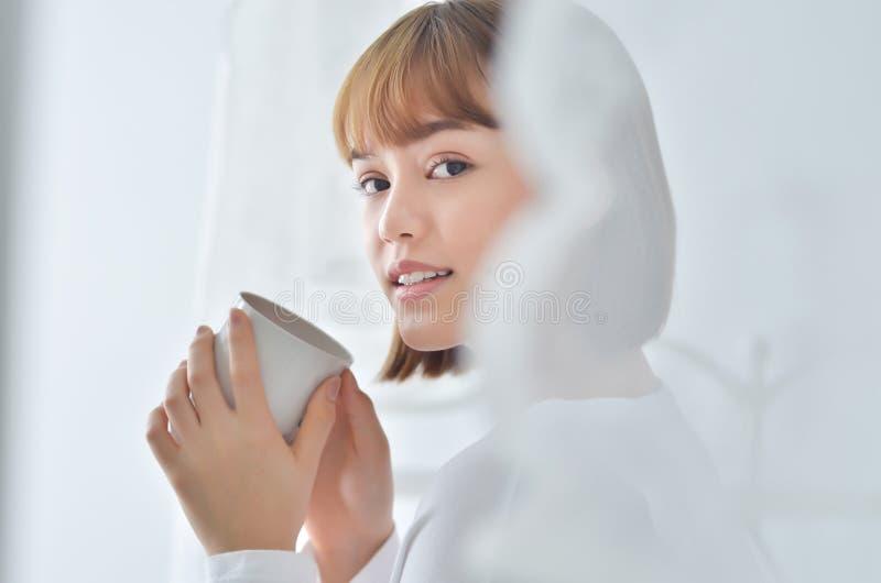 妇女在早晨庭院里喝咖啡 免版税库存图片
