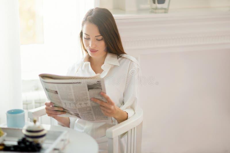 妇女在早餐期间的读书新闻 免版税库存图片