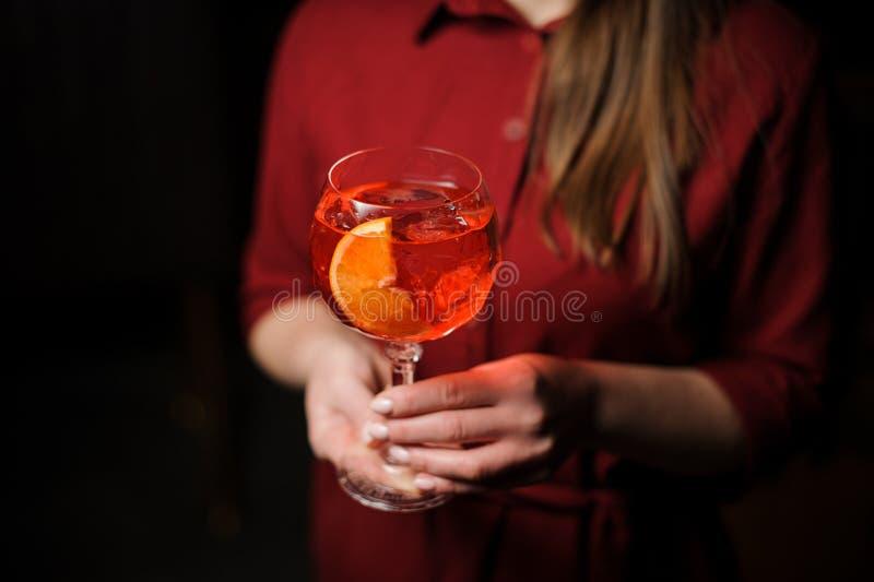 妇女在有一个鲜美Aperol注射器夏天鸡尾酒的一件红色衬衣穿戴了 免版税库存照片