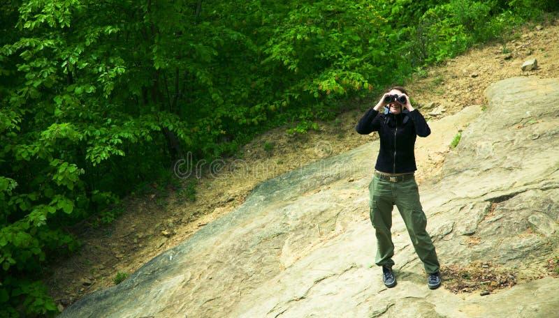 妇女在有双筒望远镜的森林里 库存照片