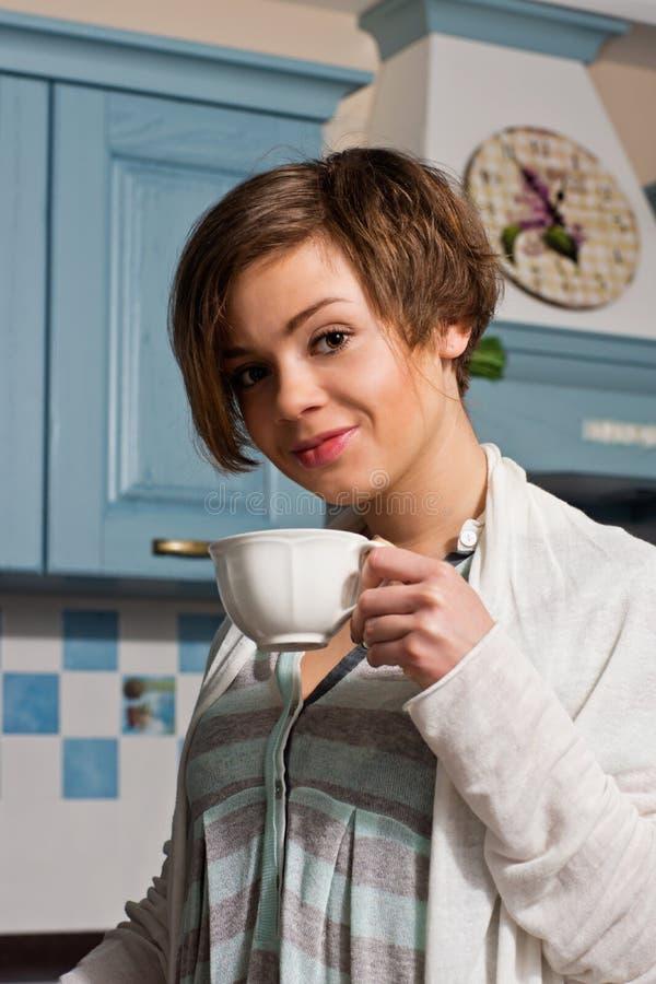 妇女在有咖啡杯的厨房里 免版税库存照片