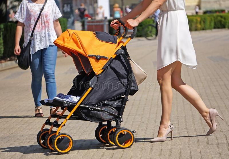 妇女在有婴儿车的街道上走 免版税库存照片