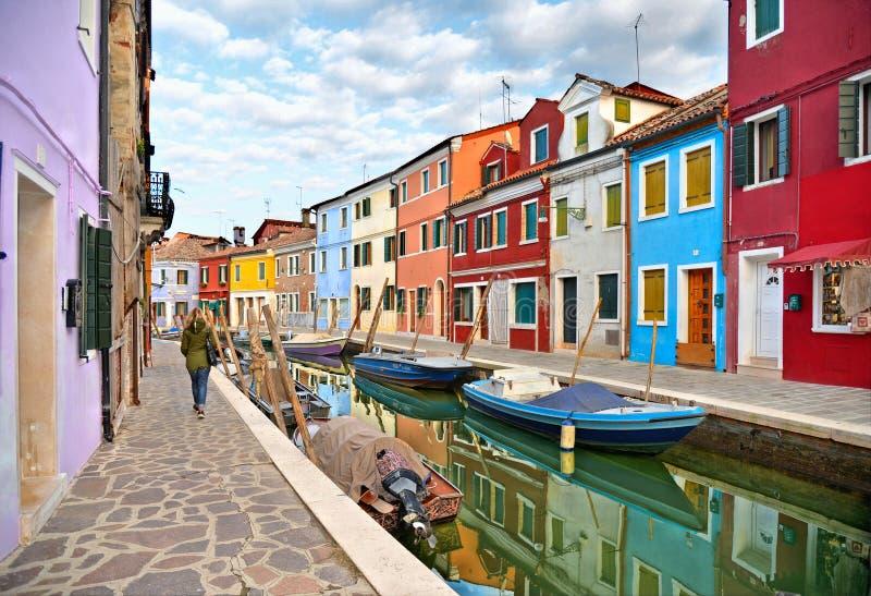 妇女在有小色的房子的行的,有fishermans小船的水运河,c Burano海岛美丽如画的街道走 免版税库存图片