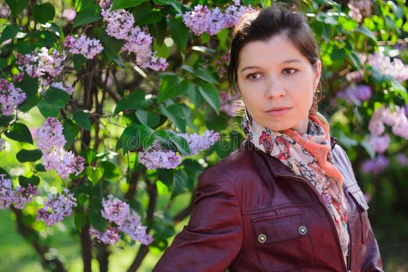 妇女在有开花的丁香的3春天庭院里 库存照片